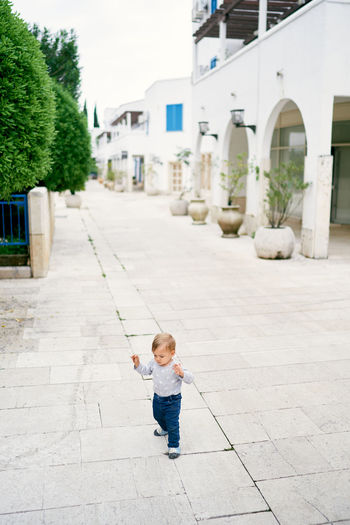 Boy standing on footpath against building