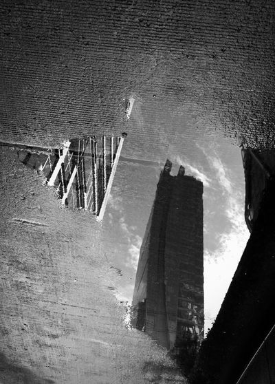 high angle view of hotel skyscraper in water reflection of a puddle on street after raining day. After The Rain Looking Down The Week On EyeEm Water Reflections Architecture Black And White Blackandwhite Photography Building Exterior Built Structure City Concrete Day High Angle View Hotel View Monochrome Nature No People On Street Outdoors Puddle Puddle Reflections Sky Skyscraper Street Photography Water