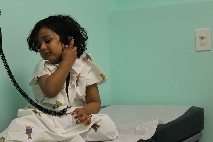 Boy using telephone while sitting on bed in hospital