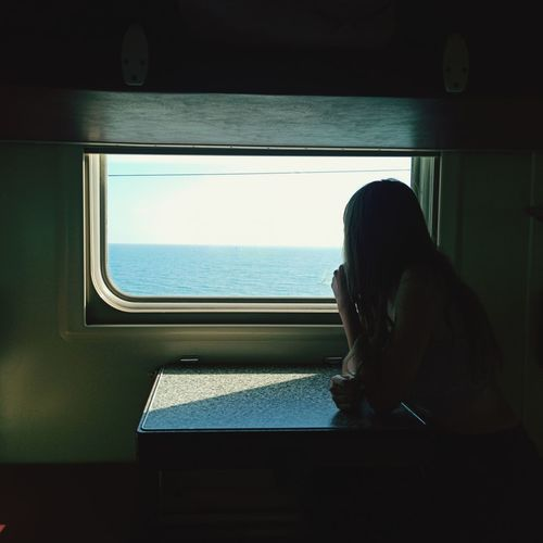 Side view of woman looking through window on tne sea