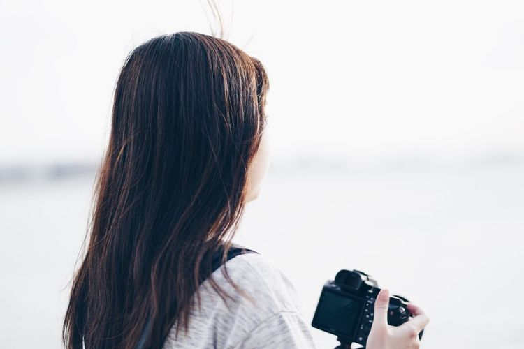 Rear view of woman holding camera at beach