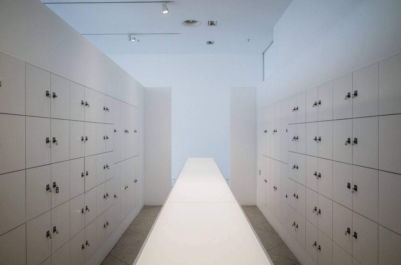 indoors, no people, architecture, white color, building, in a row, built structure, absence, wall - building feature, locker, dressing room, diminishing perspective, security, furniture, safety, corridor, storage compartment, protection, number