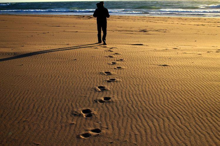 Rear View Of Man Walking At Sandy Beach During Sunset
