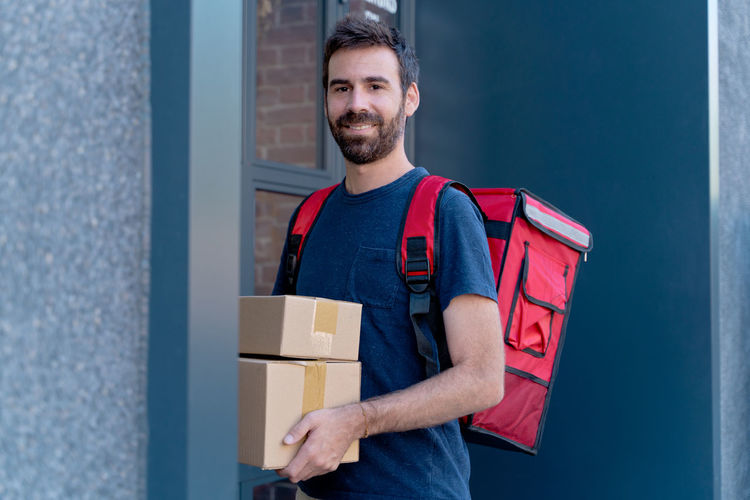 Portrait of smiling mid adult man standing in box