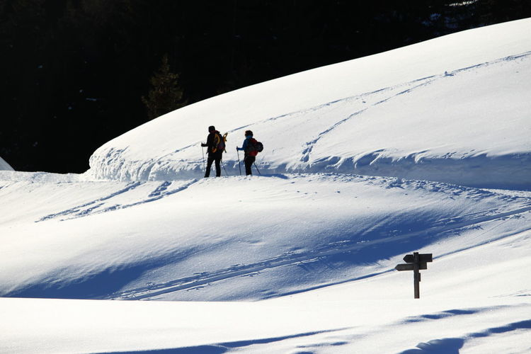 People walking on snow covered mountain
