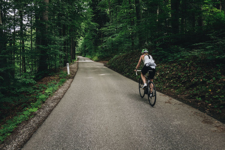 Woman riding her roadbike on road in the austrian alps