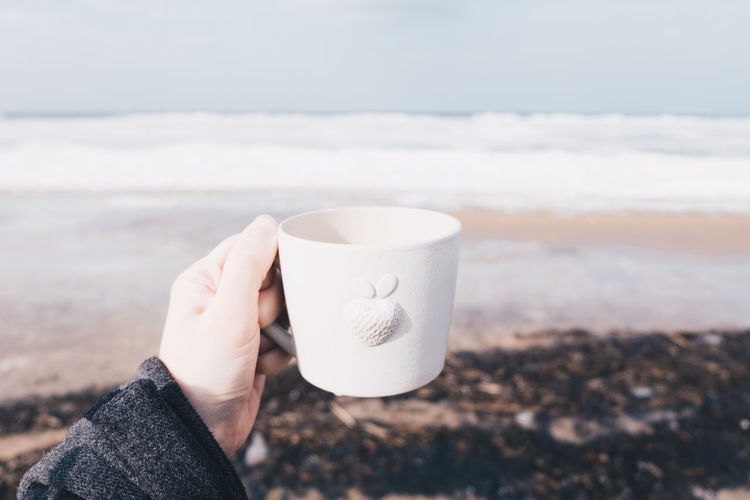 Beach Close-up Coffee - Drink Coffee Cup Cup Day Drink Focus On Foreground Holding Human Body Part Human Hand Lifestyles Nature One Person Outdoor Photography Outdoors People Real People Sea Seaside Sky White Women