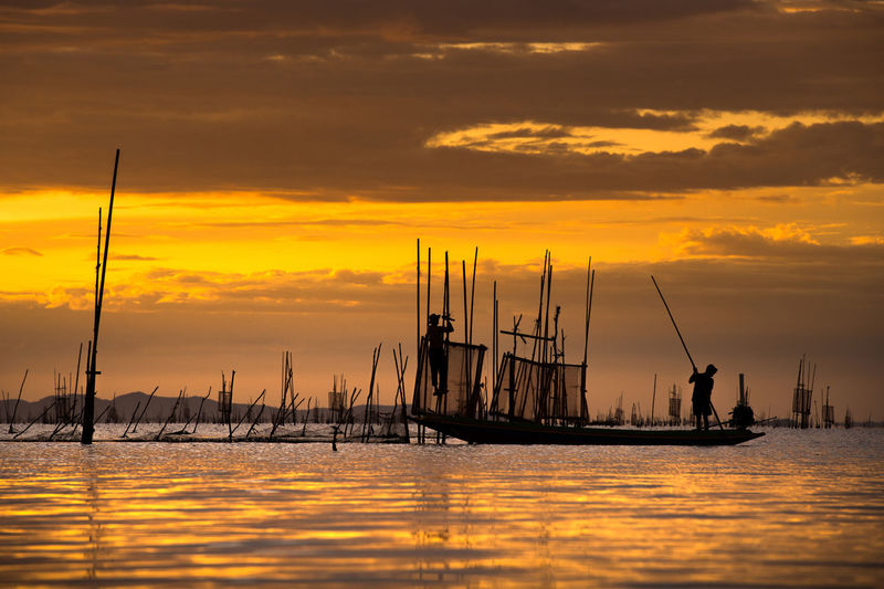 Sunset with fisherman catching fish ASIA Agriculture Coastline Dramatic Sky Harbor Thailand Travel Vietnam Boat Cultures Destination Fisherman Fishing Journey Landscape Laos Myanmar People Scenics Scenics - Nature Seascape Sky Sunrise Sunset Travel Destinations