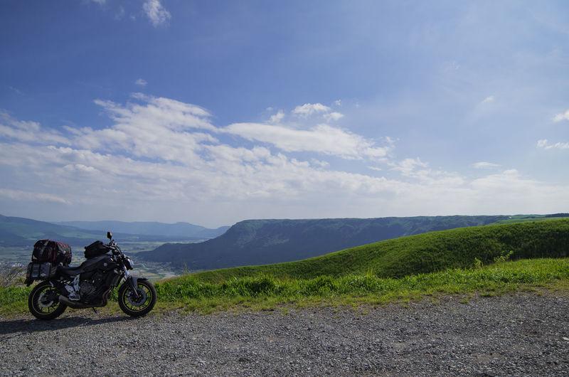 Motor bike on road by mountain against sky