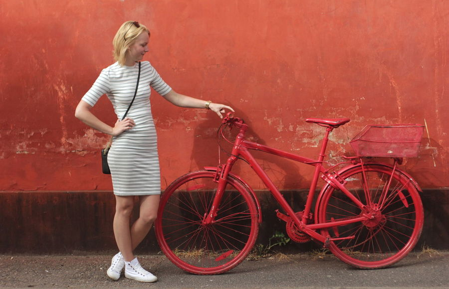 Color Contrast Full Length Portrait Girl Hanging Out Model Parked Parked Bicycle Playing Around Posing Red Bicycle Red Bicycles Red Color Stripped Dre Unusual Bicycle Wall White Dress