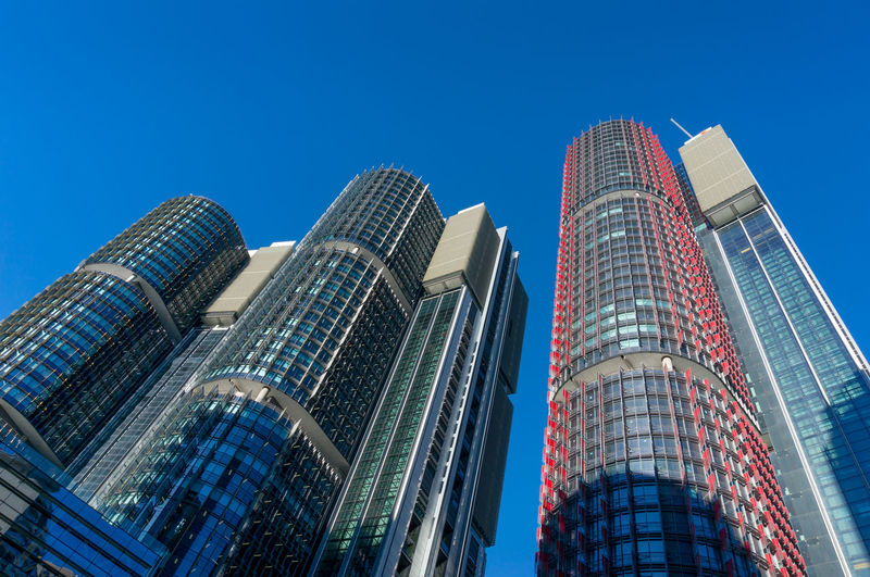 Low angle view of modern buildings against blue sky.