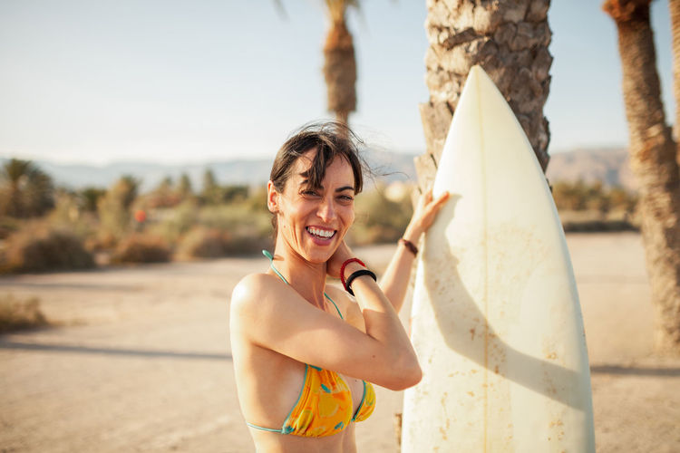 Portrait of smiling woman with surfboard standing at beach