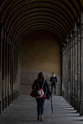 Rear view of women walking on corridor of building