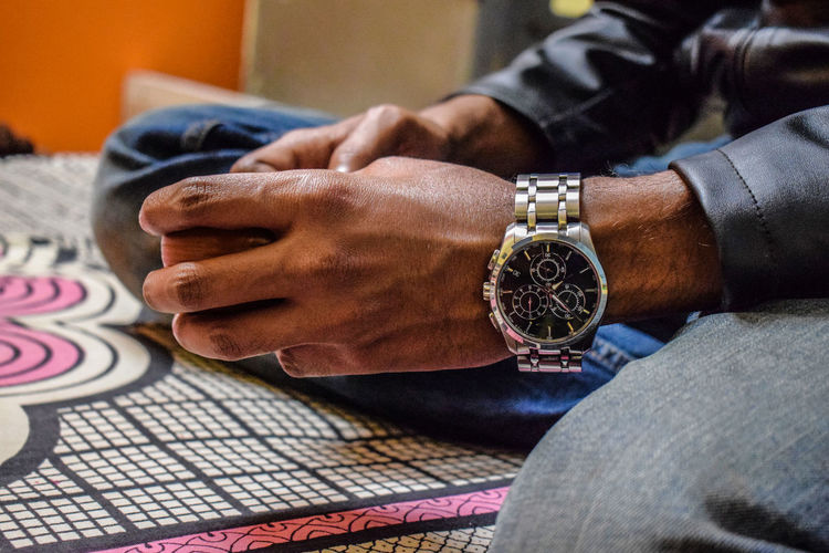 Close-up of man wearing wristwatch on bed at home