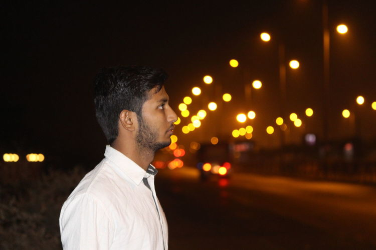 Side view of man standing outdoors at night