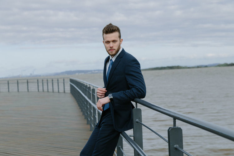 Portrait Of Handsome Man Leaning On Railing Against Sea