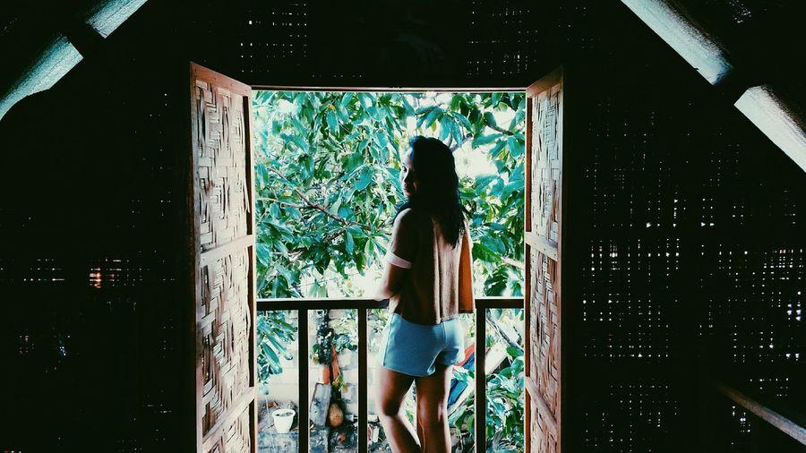 Rear view portrait of woman standing in balcony