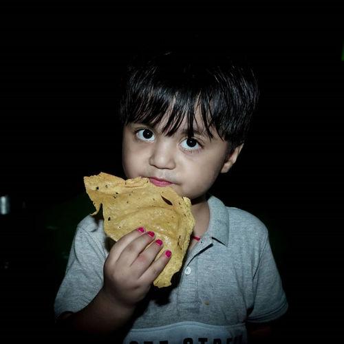 Portrait of boy holding ice cream against black background