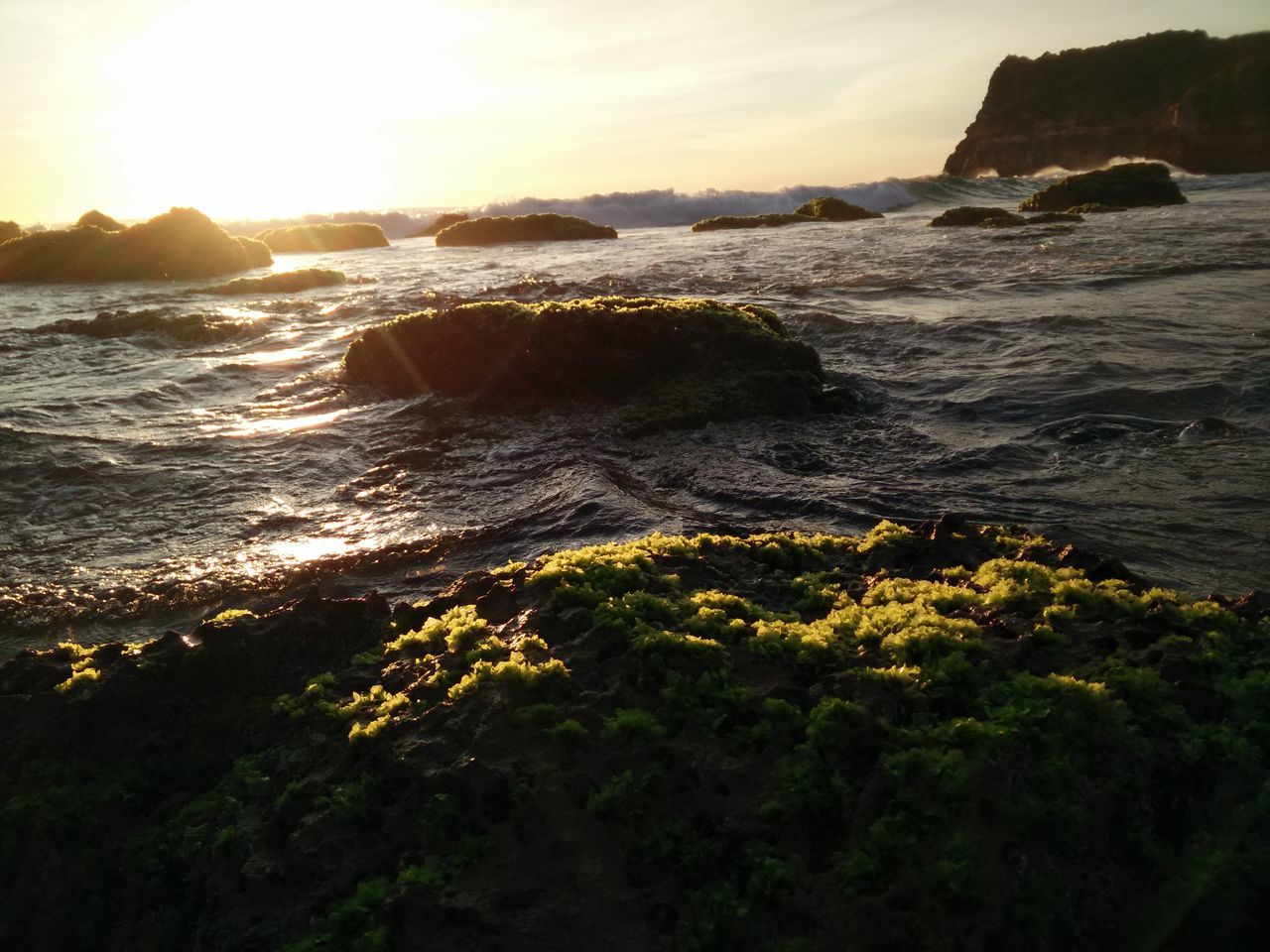 sea, nature, beauty in nature, water, sunset, sunlight, wave, rock - object, no people, scenics, beach, outdoors, tranquility, sky, horizon over water, power in nature, day