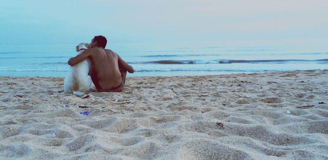 Man with dog sitting on beach