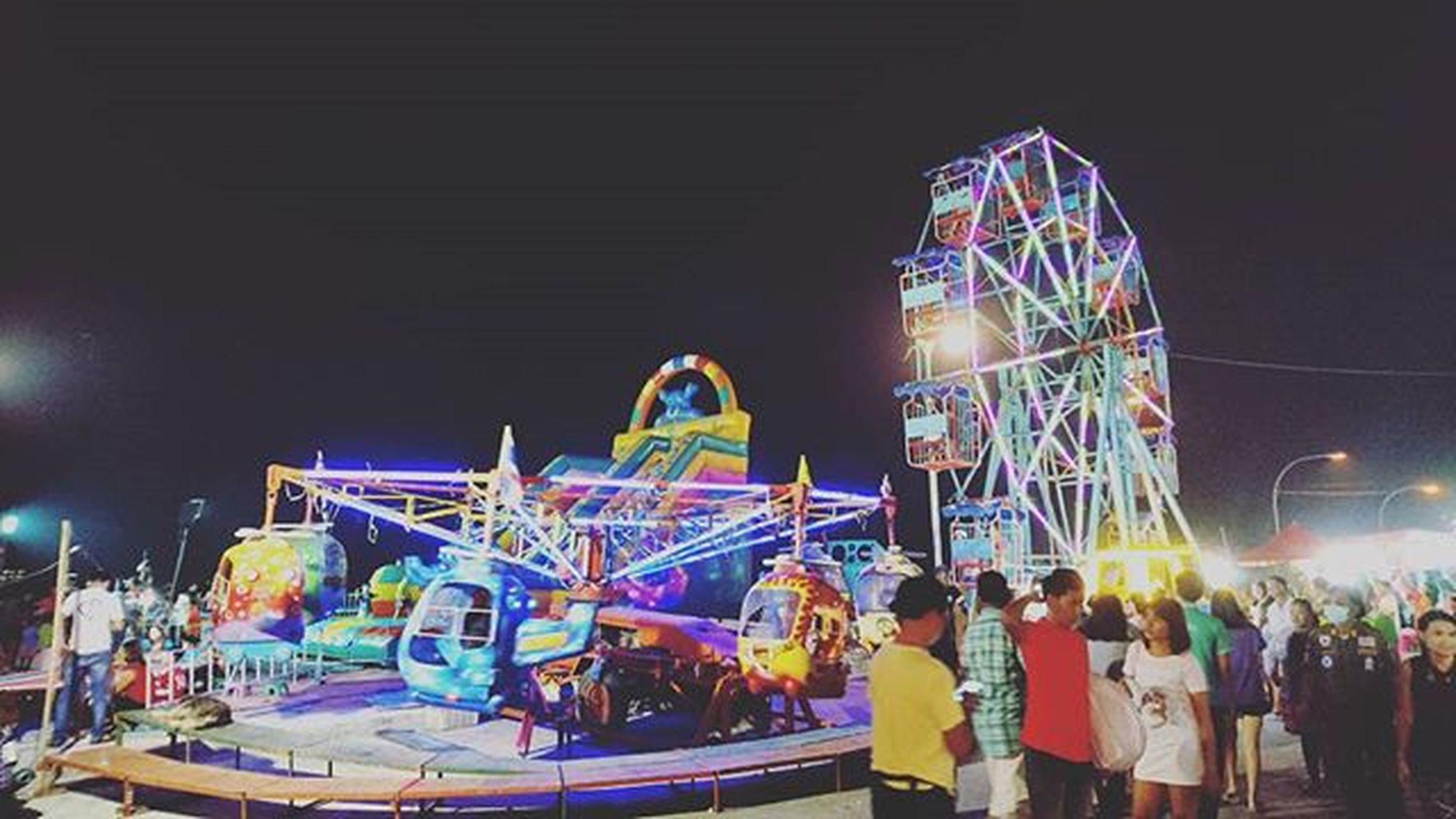 illuminated, night, amusement park, built structure, multi colored, architecture, large group of people, amusement park ride, arts culture and entertainment, leisure activity, building exterior, city, men, lifestyles, lighting equipment, city life, person, incidental people, enjoyment