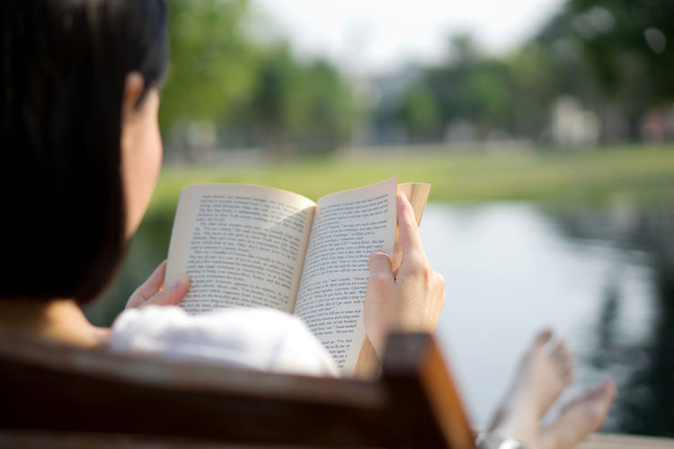 Midsection of man reading book against blurred water