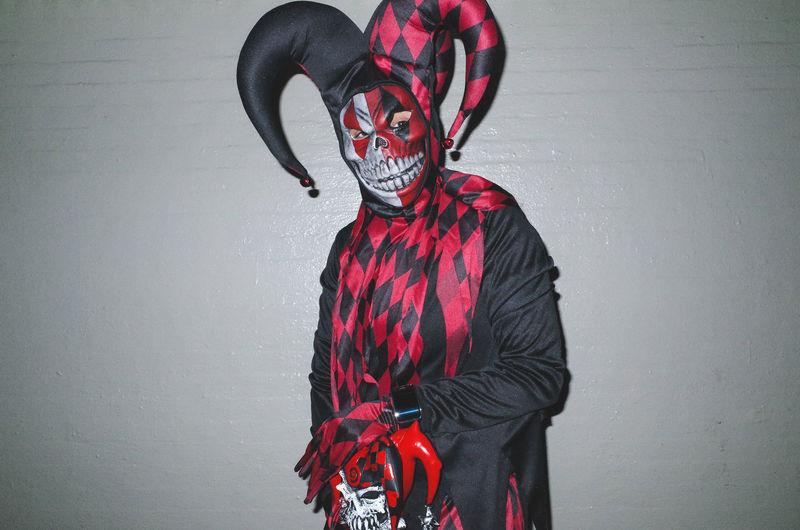 Red and black clown costume. Black Candid Clown Costume Flash Halloween Mask New York City Night Parade Portrait UNPOSED