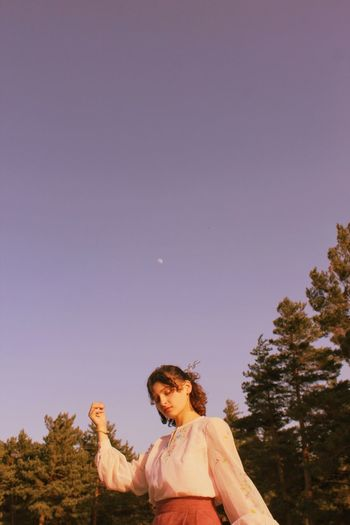 Low angle view of woman standing against clear sky