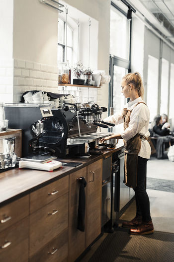 Woman standing by coffee in kitchen