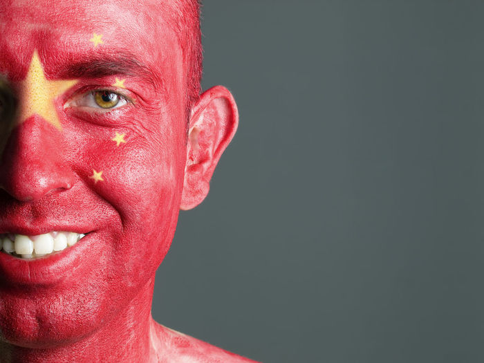 Close-up portrait of smiling man with chinese flag body paint against gray background
