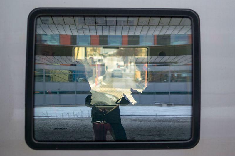 Man photographing through train window