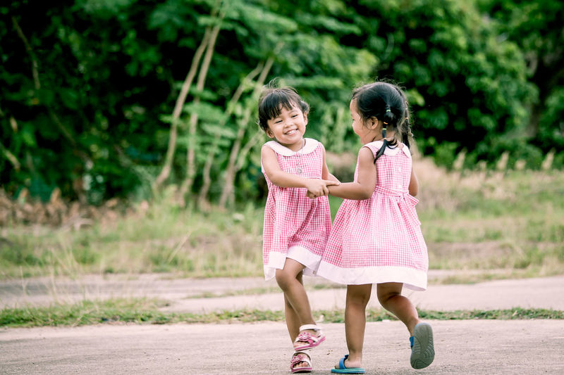 Twin sisters playing at public park