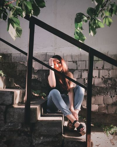 Woman looking away while sitting on steps by wall