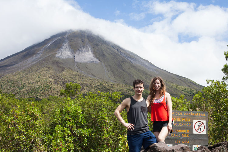 Young couple standing by sign against volcano