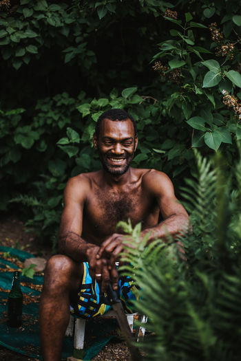 Shirtless man smiling while sitting in yard