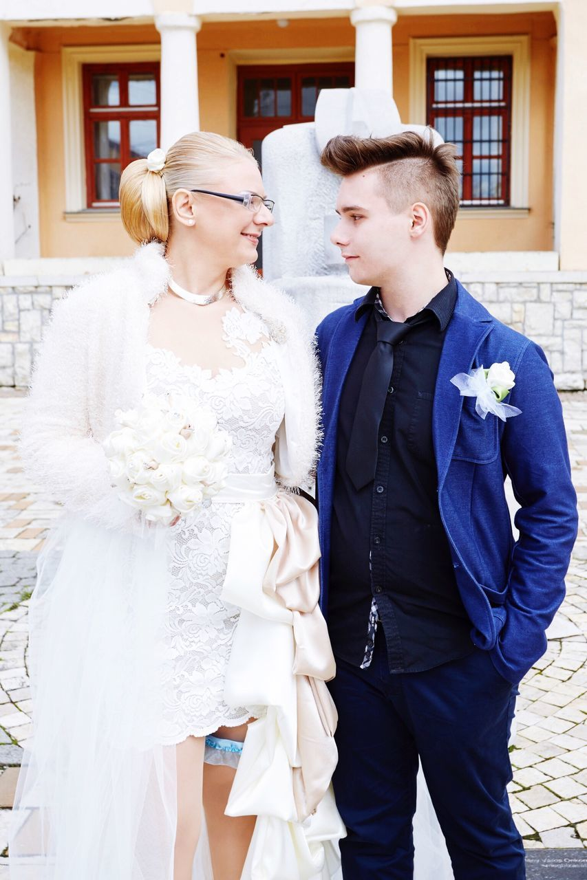 Boy Looking At Mother Wearing Wedding Dress Standing Outside Building