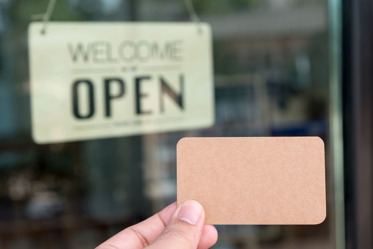 Cropped Image Of Hand Holding Business Card Against Information Sign Seen Through Glass Window