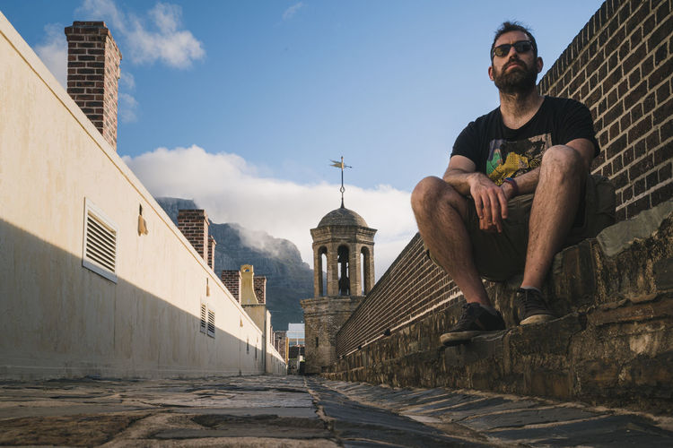 Young adult sitting on the walls of cape town castle