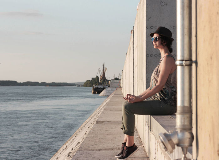 Full length of woman sitting on wall by river