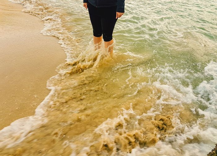Leggs of woman  in the seewater with waves on beach
