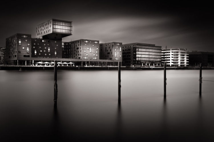 Wooden Posts On River Against Buildings In City At Night