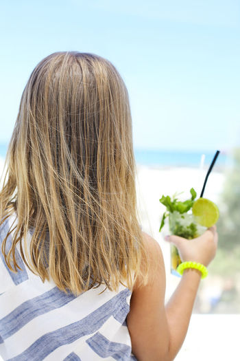 Rear view of woman holding apple at beach against sky