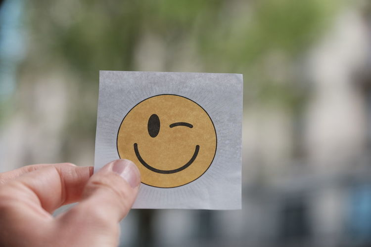 Close-up of hand holding anthropomorphic smiley face on paper