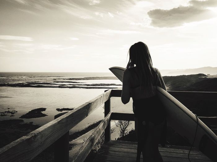 Rear view of woman with surfboard standing at beach against sky