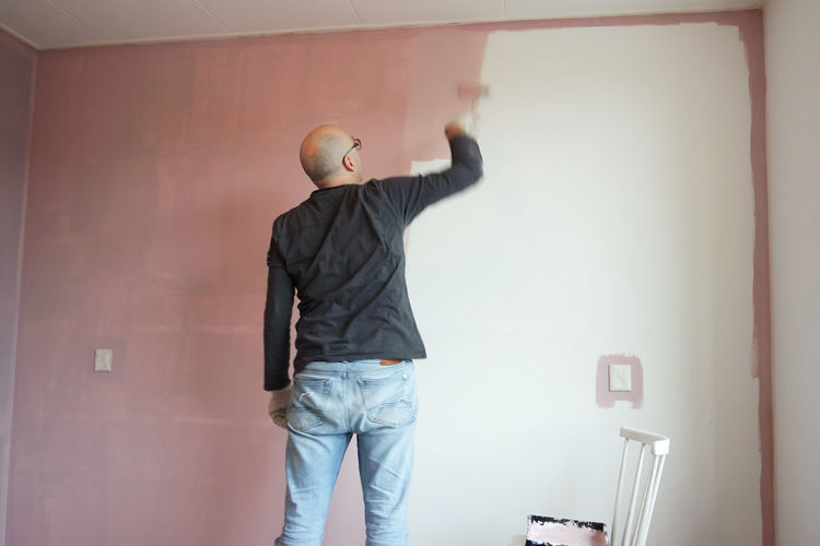 One Person Rear View Standing Indoors  Wall - Building Feature Casual Clothing Men Adult Three Quarter Length DIY Home Improvement Working Home Interior Arms Raised Mid Adult Paint Human Arm Lifestyles Human Limb Jeans