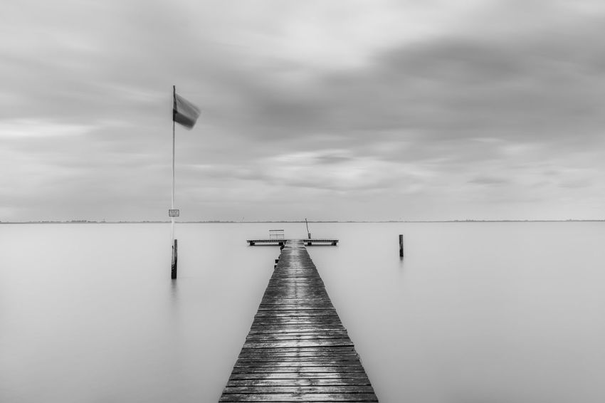Water Sky Cloud - Sky Pier The Way Forward Tranquility Sea Tranquil Scene Direction Scenics - Nature No People Beauty In Nature Nature Wood - Material Day Flag Jetty Outdoors Built Structure Horizon Over Water Diminishing Perspective Wooden Post Long