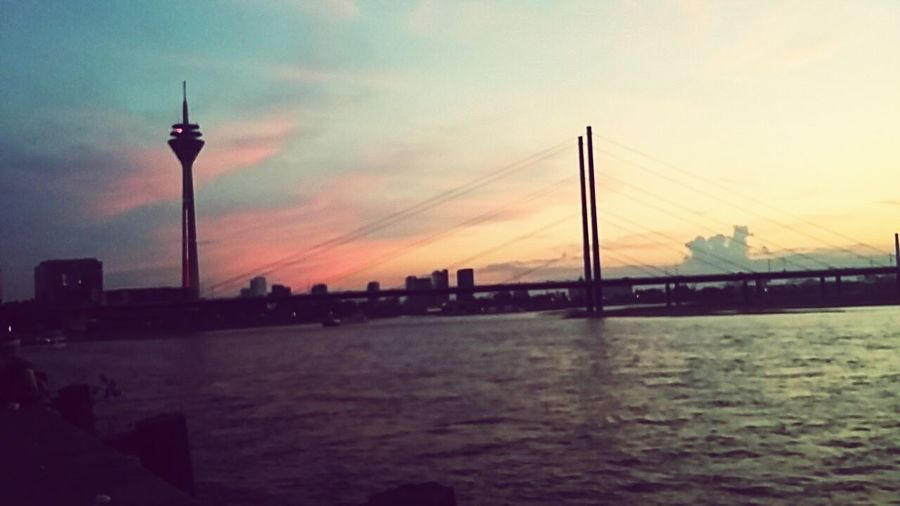 Battle Of The Cities Bridge - Man Made Structure Water Waterfront Cloud Sky Bridge Sea Suspension Bridge Calm Nature Tranquil Scene Outdoors Architecture Built Structure Orange Color Düsseldorf Düsseldorf ♡ Düsseldorf-Walk Düsseldorf, Medienhafen First Eyeem Photo House Street Road No People