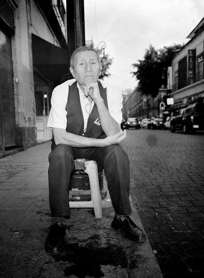 Portrait of a man sitting on built structure