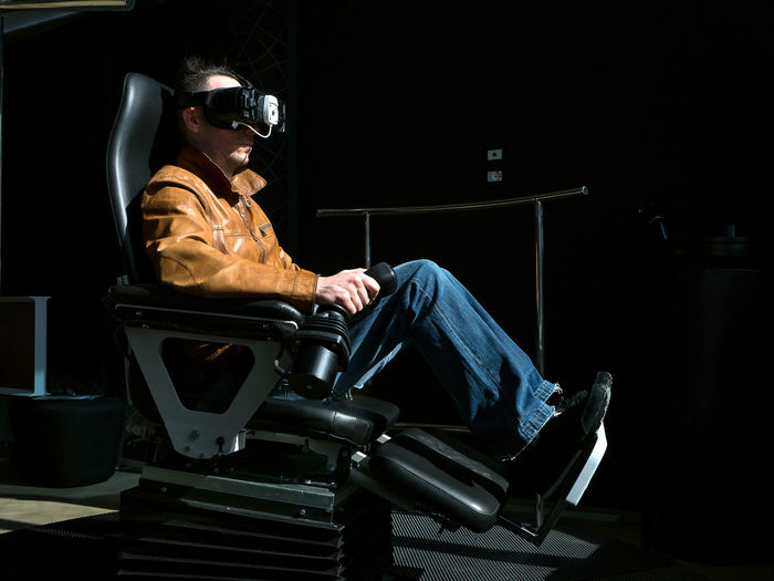 Side view of man playing virtual reality game on seat