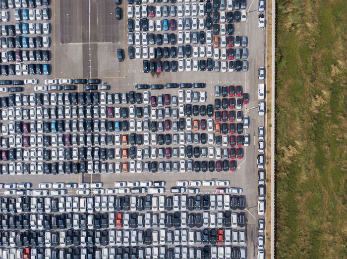 High angle view of cars in parking lot by building